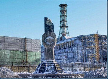 Chernobyl disused reactor_enclosed in a concrete and lead sarcophagus_In the foreground is a memorial to workers who died trying to contain the radiation