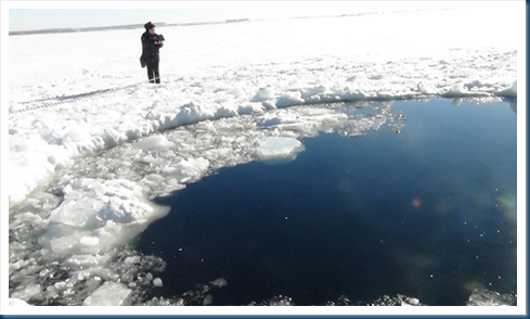 Image Credit: A circular hole in the ice of Chebarkul Lake where a meteor reportedly struck the lake near Chelyabinsk (AP)